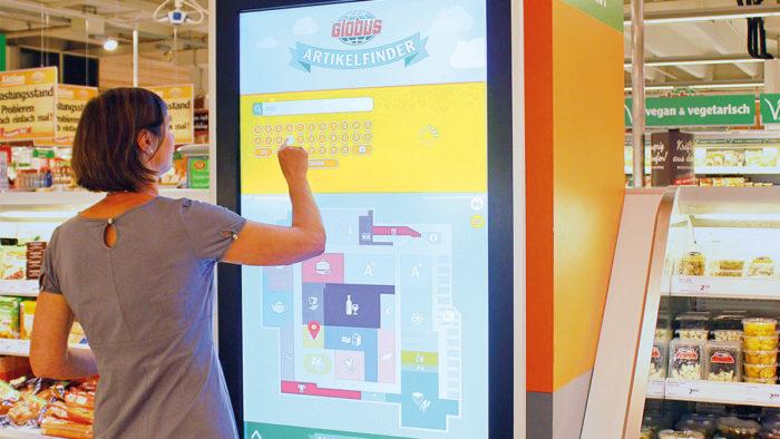 """Terminal mit """"Artikelfinder"""": Die Kundin gibt die Produktbezeichnung alphabetisch ein, der Ort im Markt wird angezeigt."""