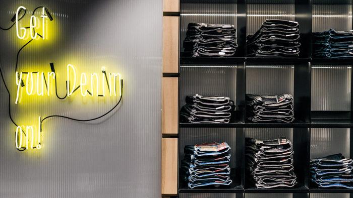 Bei Infected, einem Shop im österreichischen Department Store Kastner & Öhler, setzt gelb strahlende Neonschrift auf dunklen Wänden kräftige Akzente