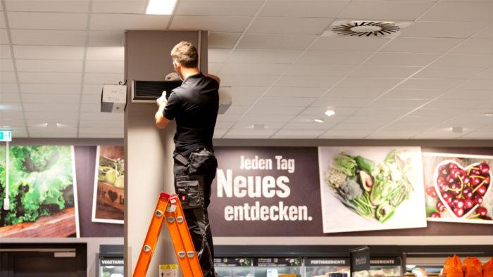 Die Umluft-Desinfektionsgeräte werden an Säulen und Wänden im Supermarkt installiert.