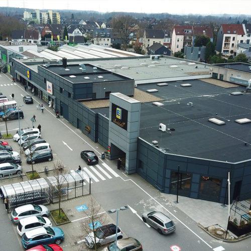 Eine dunkelgraue Streckmetallfassade bildet die Kulisse für den Edeka-Supermarkt und die anderen Ladenmarken im Fachmarktzentrum