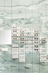Die Brillenwand in Berlin wurde aus vier Tonnen grünem Cipollino-Marmor gefertigt. In anderen Filialen kommt zum Beispiel Aluminium, Kork oder Sandstein zum Einsatz