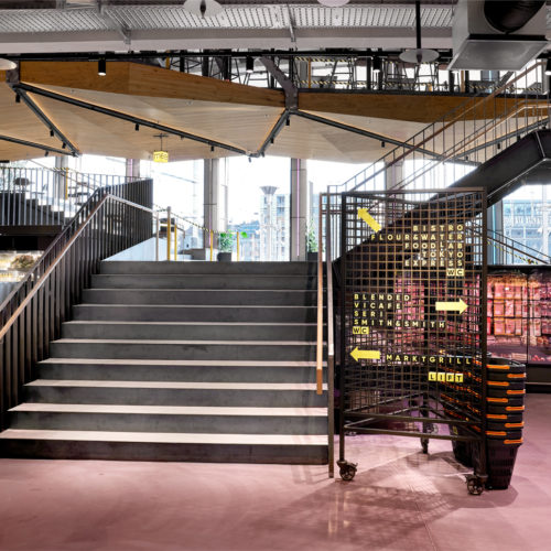 Urban: schwarze Gitterelemente mit gelben Neonpfeilen, die die Kundschaft navigieren