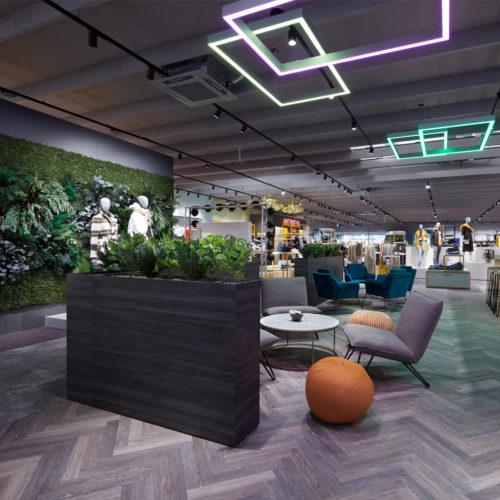 Begrünte Rückwände und eine Lounge mit wohnlichem Mobiliar sollen die Aufenthaltsqualität im Store erhöhen.