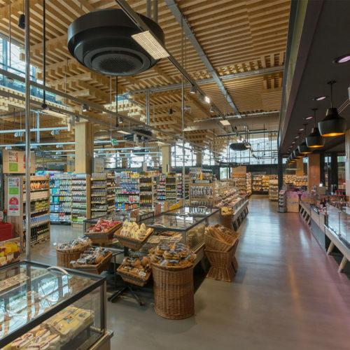 Eine stapelförmige Holzkonstruktion bildet das Grundgerüst des 1.500 qm großen Rewe-Marktes in Wiesbaden.
