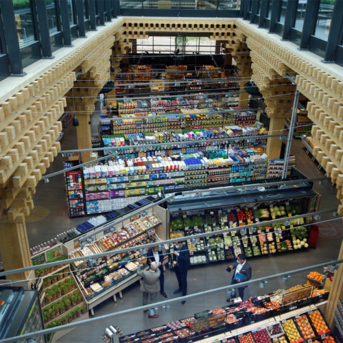 Viel Tageslicht, großzügige Höhen, das gläserne Dach sowie die gewölbte Holzkonstruktion schaffen ein Marktplatz-Ambiente im Inneren des Pilotmarkts.