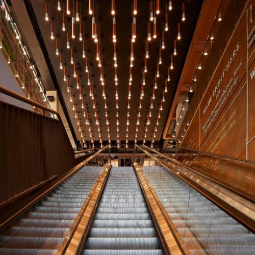 Zahlreiche Lichter zieren die Decke über der Rolltreppe.