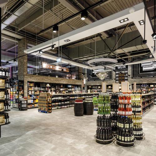 Die überdimensionale Leuchte im Industrial-Style setzt das Weinsortiment in Szene.