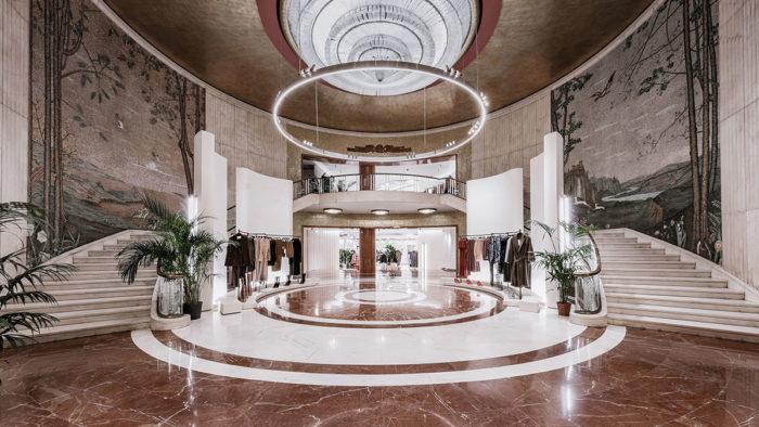 Das große Eingangsatrium mit zweizügiger Treppe, Marmorboden und Deckenleuchter aus Murano-Glas.