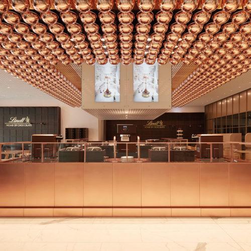 Das Café mit seinen 80 Sitzplätzen und Außenterrasse in den Corporate Colours Kupfer und Schokoladenbraun.