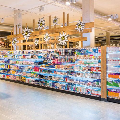 """Auch in der Drogeriewarenabteilung: klare Linien mit Deko-Elementen aus Holz und der """"Landesblume"""" Edelweiß"""