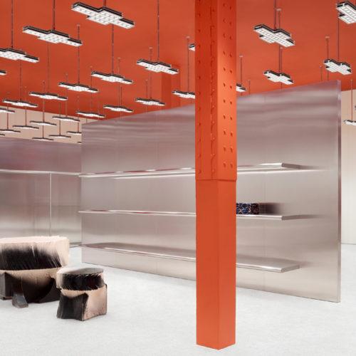 """Dieser charakteristische Rotton ist es auch, der das minimalistische Interior-Konzept dem Standort gemäß personalisiert. Neben den Fenster- und Türrahmen wurden auch die Decke sowie die Stützpfeiler im Raum in """"Golden-Gate-Bridge-Rot"""" gestrichen. Weltweit ist das Storedesign der Premium-Marke Acne Studios von Edelstahl-Wänden, Neon-Licht und einzelnen Design-Möbelstücken geprägt. Hier wurden die Einbauten weitgehend zurückgefahren, um die Raumwirkung mit einer Fläche von rund 260 qm zu voller Geltung zu bringen. (Foto: Acne Studios)"""