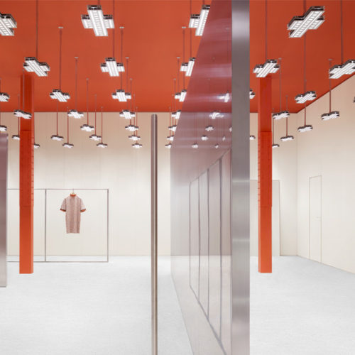 Der Raum entfaltet so seine industrielle Anmutung, unterstützt durch den gegossenen Betonboden und Wände, die vom Boden bis zur Decke mit Polycarbonatplatten in einem milchigen Weißton verkleidet sind. Eine freistehende Aluminiumwand gegenüber dem Eingang durchquert den Raum: Sie trägt die Aluminium-Fachböden für die Legeware. Die Leuchten, die in gleichmäßigem Raster von der viereinhalb Meter hohen Decke hängen, wurden speziell für den Store designt. (Foto: Acne Studios)