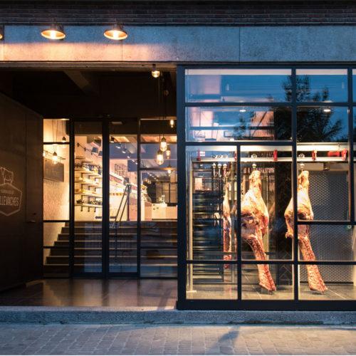 Moderne Metzgerei-Ladenfront im Industrie-Chic: ein stählernes Rolltor und Rinderhälften (Foto: Bäro)