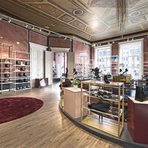 Herzstück des architektonischen Konzeptes ist der ehemalige Speisesaal des Hotels in der ersten Etage, der als Schuhsaal neu interpretiert wurde. Die Wandverkleidungen in Stucco Lustro und die aufwändige Decke mit Kassettengliederung und Medaillons mit Arabesken, phantastischen Tiergebilden, Früchten und Pflanzenmotiven lieferten die Vorlage für das durchgängige Farbkonzept. Warme Rot-, Gold-, Erd- und Grautöne ziehen sich vom Schuhsaal in den Nebenraum – dem heutigen Trachtenkabinett – bis ins Erdgeschoß. (Foto: Umdasch Shopfitting)