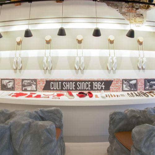 Die gegenüberliegende Wand widmet sich dem Spirit des 1964 entwickelten und zurzeit wieder als Trendmodell gefragten Schuh-Klassikers und der Tradition des Schuhmacherhandwerks mit diversen Ausstellungsstücken – und bietet Platz für einige voluminöse Sessel für die Schuh-Anprobe. (Foto: Grashopper)