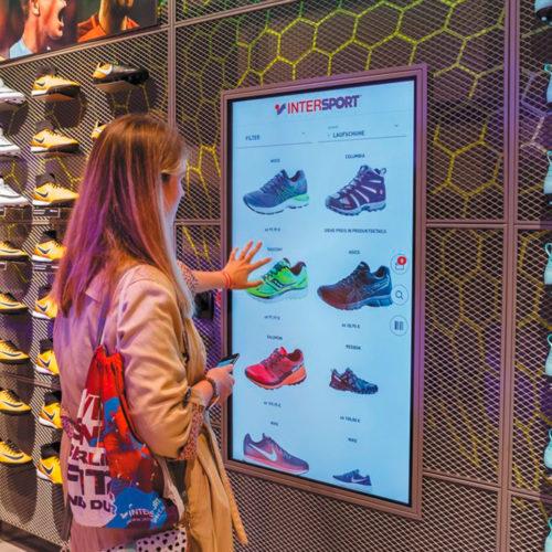 In jeder Abteilung dienen Touchscreens als Regalverlängerung (Foto: Intersport)