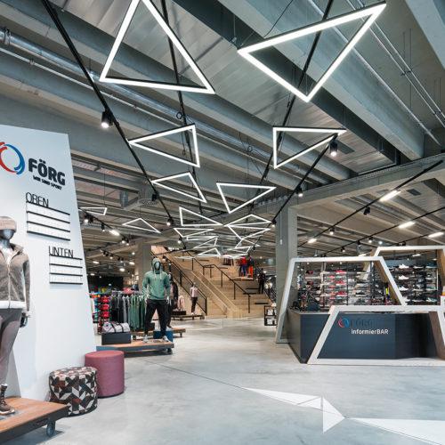 Leuchten in geometrischen Formen navigieren den Kunden durch den Store.