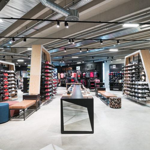 Mit Holz verkleidete Warenträger durchbrechen das raue, industriell geprägte Interieur.