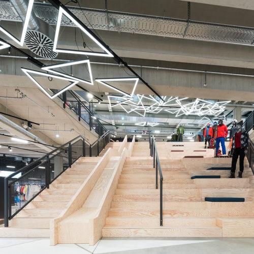 Mittelpunkt des Stores und zugleich verbindendes Element beider Etagen: die bis zu 11 Meter breite Treppe aus Seekiefer